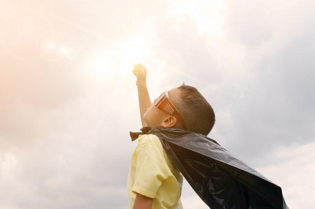 дете облечено с мантия на супер герой
